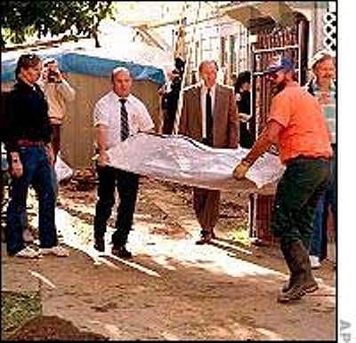 Vyšetřovatelé vynášejí ostatky obětí nalezené zakopané na dvorku za domem.