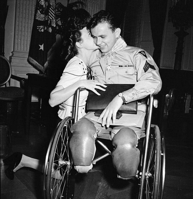 7. Jean Moore klečí a objímá svého snoubence, veterána 2. světové války, Ralpha Neppela, který byl vyznamenán Řádem cti a Purpurovým srdcem, 1945