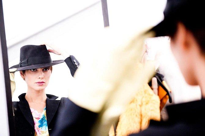 Modelka, která předvádí i pro značku Galliano, se kontroluje v zrcadle okamžik předtím, než ji spatří tisíce očí