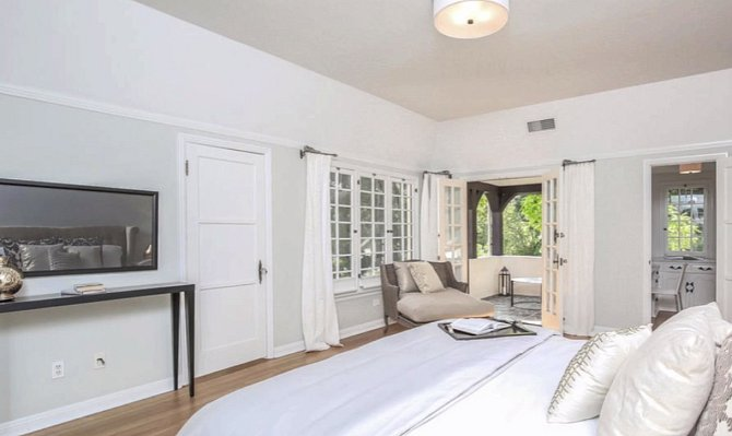 Ložnice je zařízena velmi elegantně a v čisté bílé barvě.