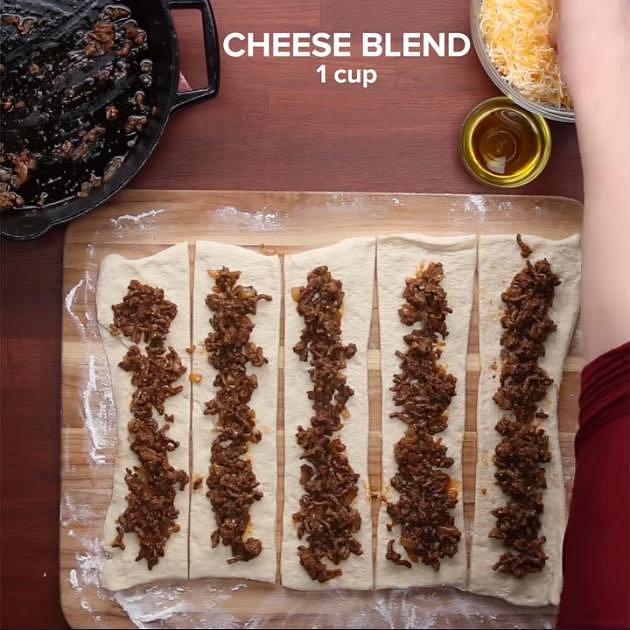 Těsto na pizzu si rozřízněte na 5 dílů. Na každý kousek dejte část masa.