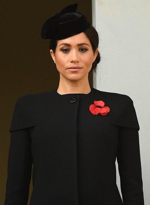 Meghan zvolila černý umírněný kabátek s tradičním vlčím mákem.