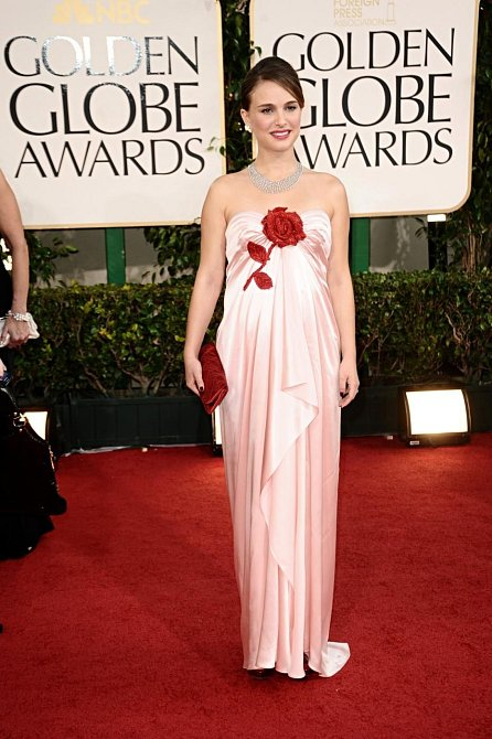 Natalie Portman si přišla pro druhý Zlatý glóbus v něžných šatech se stylizovanou červenou růží – stejnou barvu má také večerní kabelka. Hádali byste pod řasenou látkou bříško s miminkem?