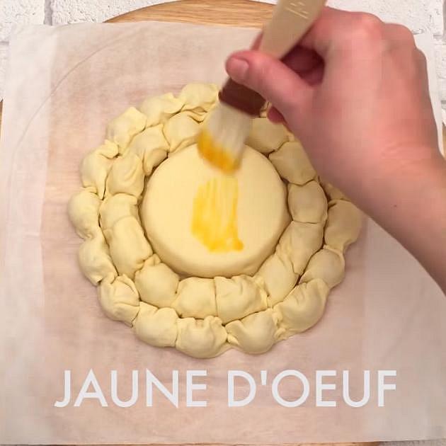 Párečky opět zabalte do naříznutých plátků těsta a stočte je k sýru. Pomažte našlehaným žloutkem a posypte mákem a sezamovým semínkem. Dejte péci do předem vyhřáté trouby na 180 °C na cca 40 minut.