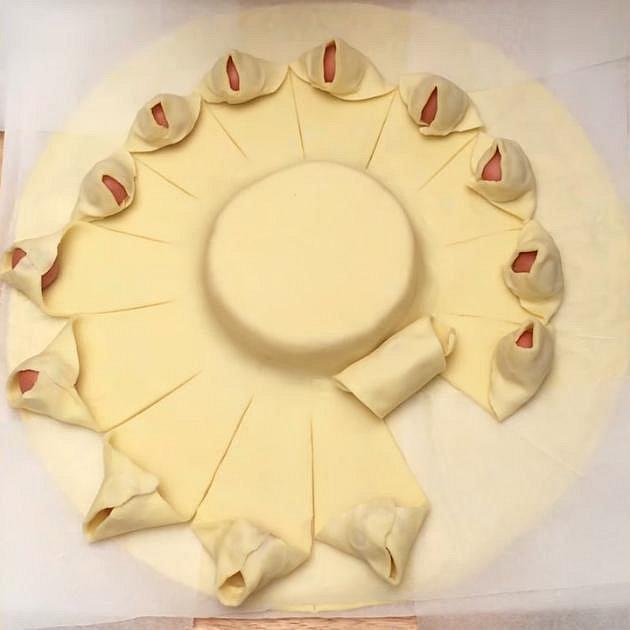 Zabalte malé párečky do naříznutých plátků těsta a stočte je k sýru. Odkryl se vám tak pečící papír, který jste tam předtím vložili. Odstraňte jej.
