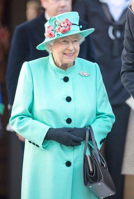 Tyrkysový kabát a květinová dekorace na klobou.
