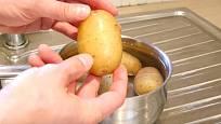 Uchopte bramboru a jemně zatlačte na slupku, ucítíte, jak vám začne pod rukama klouzat.