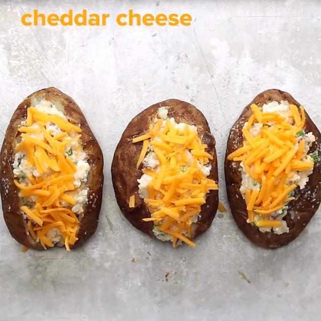 Vše dobře promíchejte a směs vložte zpět do vydlabaných brambor. Posypejte zbylým nastrouhaným sýrem a zbytkem opečené slaniny. Pečte při 180 °C cca 25 minut.