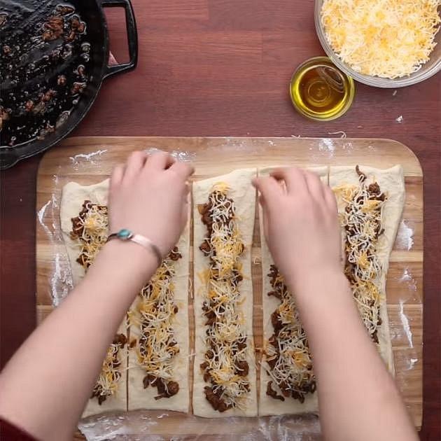 Každý kousek hustě posypte sýrem dle chuti. V receptu použili smíchaný cheddar s mozzarellou.