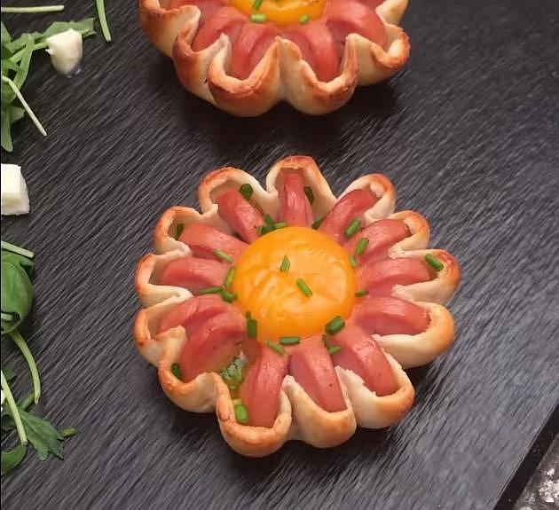Slané koláčky - Co budete potřebovat: 4 jemné párky, listové těsto (nebo to na pizzu), tvrdý sýr, 4 vejce, jarní cibulku, pepř a sůl