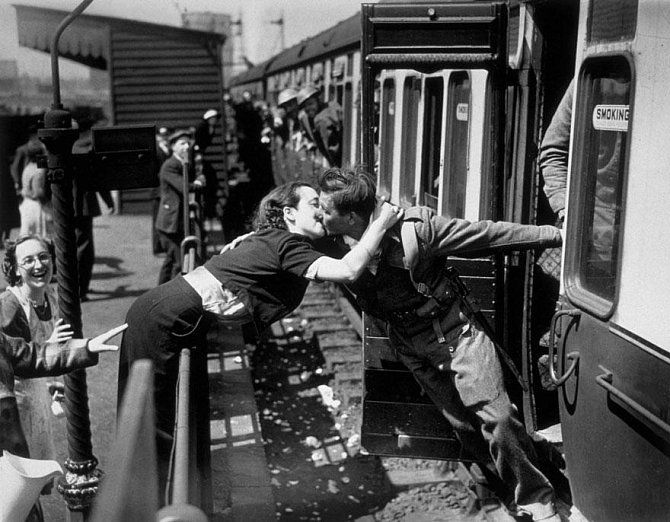 6. Mladá britská žena se naklání přes zábradlí, aby mohla políbit svého přítele, který se vrací z fronty, 2. světová válka, Londýn, 1940