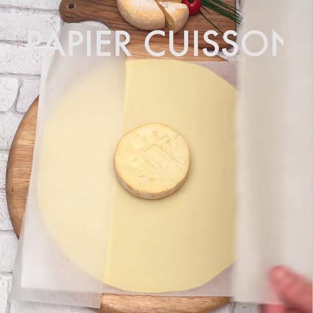 Položte ho na plát listového těsta a na těsto rozložte pečící papír. Sýr a papír zakryjte stejně velkým druhým plátem listového těsta a kolem sýru ho upěchujte.