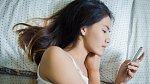 Ilustrační foto - žena odpovídající na SMS v posteli