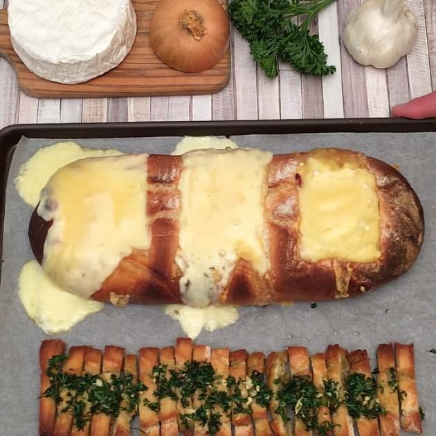 Chléb se třemi druhy sýrů - Co budete potřebovat: celý chléb, sýr Camembert, sýr Reblochon, sýr Raclette, zkaramelizovaná cibulka, rozmarýn, opečená slanina na kostičky, olivový olej, česnek, petrželku, sýr Parmezán a trochu soli