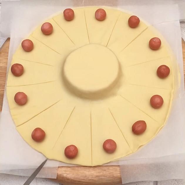 Na druhý plát položte kolem dokola malé párečky a nařízněte opatrně těsto ke středu.