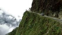 Bolivie, Jižní Amerika – Silnice, která tu lemuje úbočí horského průsmyku, patří k nejnebezpečnější na světě. Prakticky se po ní nedá bez nehody projet. Stačí jen trochu uhnout z trasy a není šance na záchranu, automobil i vás...