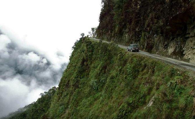 Bolivie, Jižní Amerika – Silnice, která tu lemuje úbočí horského průsmyku, patří k nejnebezpečnější na světě. Prakticky se po ní nedá bez nehody projet. Stačí jen trochu uhnout z trasy a není šance na záchranu.