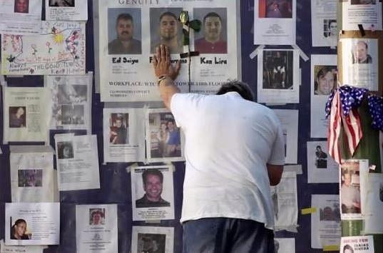 Muž truchlí u zdi s fotografiemi obětí teroristického činu z 11. 9. 2001.
