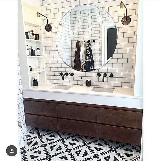 Stroze zařízená koupelná zoufale volá po výrazném doplňku, velké kulaté zrcadlo jím je.