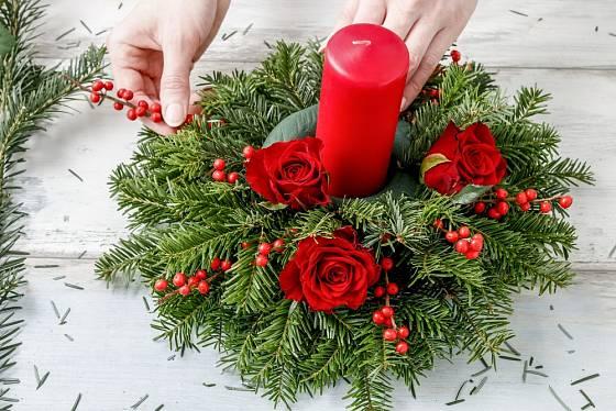 základ svícnu je z chvojí, květy růží doplňují větvičky cesmíny přeslenité s červenými bobulemi