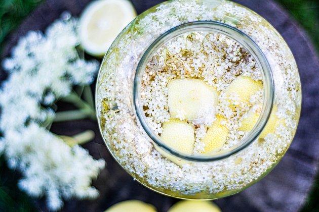 Do sklenice vložte ve vrstvách květy bezu, citrony a limetky.