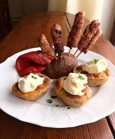 Slovinské čevapčiči se podává s grilovanými paprikami a pečenými brambory, na kterých se zvolna rozpouští kajmak.