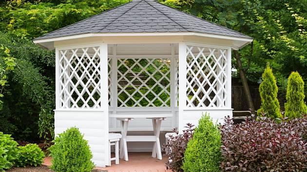 Bíle natřený dřevěný altánek působí elegantně.