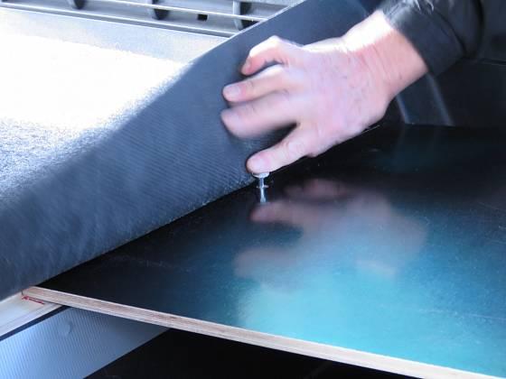 Vzadu jsou desky na trámku bedny, zajišťují je šrouby a spojení je překryté kobercem. Novější typ Citroenu Berlingo