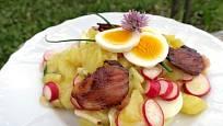 Bramborový salát s ředkvičkami přizdobený květem pažitky.