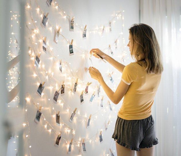 Fotky zavěšené na světelném řetězu jsou kreativním dekorativním řešením.