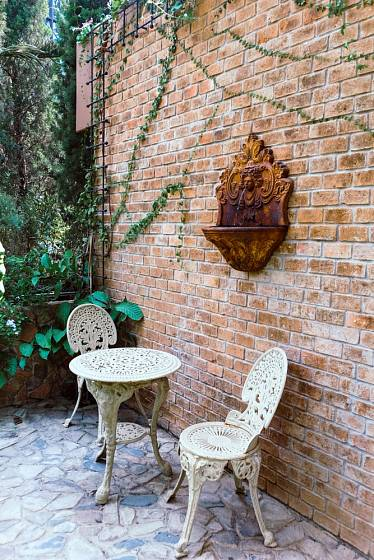Cihlová stěna a na ní věkem zašlá výlevka, která nyní slouží jako zahradní dekorace.