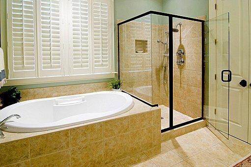 prostorný sprchový kout a vana s madlem pro usnadnění pohybu