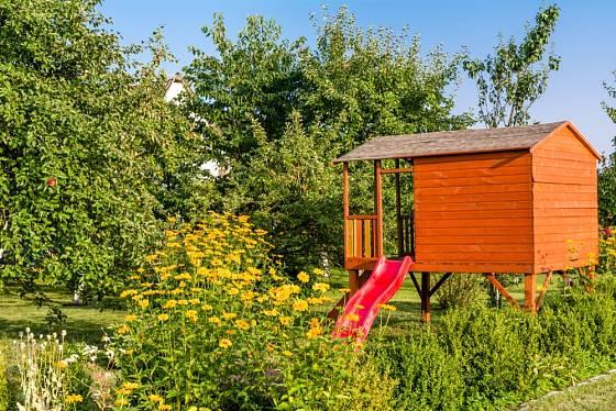 Zahradní domek pro děti doplněný skluzavkou.
