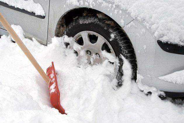 Vůz těsně u cesty nám zavalí sníh z odhrnované cesty.