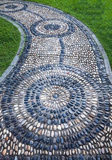 Zahradní cesta skládaná z oblázků dvou barev je vlastně zahradním uměleckým dílem.