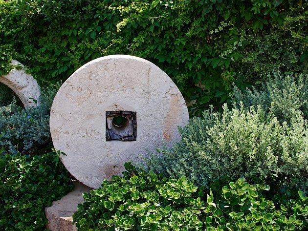 Světlé kamenné dekorace vyniknou v náruči stálezelených rostlin