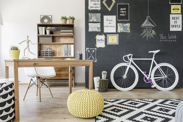 Praktická zeď v obývacím pokoji natřená tabulovou barvou.