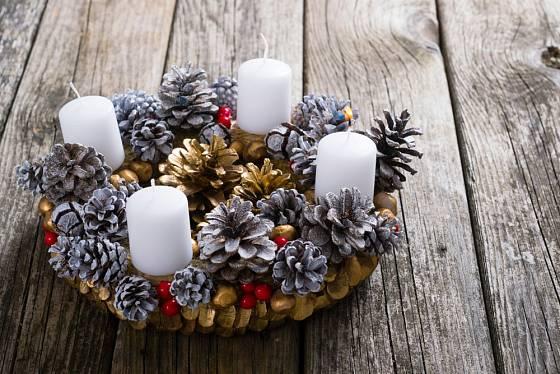 Adventní věnec zdobený šiškami a bílými svíčkami.
