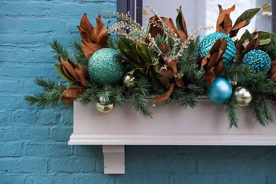 Okenní truhlík zdobíme nejčastěji chvojím a dekoracemi jako jsou vánoční baňky.
