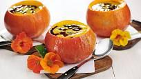 Dýňová polévka podávaná v dýni a zdobená semínky.