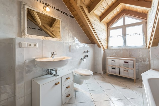 Koupelna v podkroví má dostatek přirozeného denního světla.