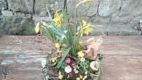 Dekorace s živými květinami, vaječnými skořápkami, vyřezávaným zajícem a peříčky.