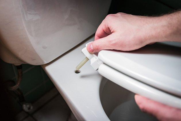Pod přišroubovanou lištou sedátka toalety se skrývá nahromaděná špína.