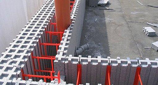Ztracené bednění z polystyrenu s plastovými spojkami (červené). Do mezery se naleje beton