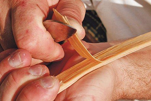 Pletař nařízne borový klát, aby oddělil jedno léto dřeva