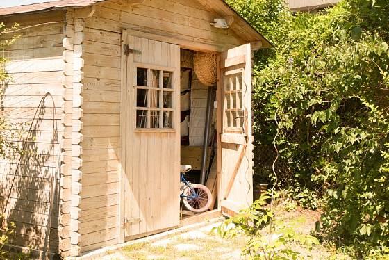 Zahradní domek na nářadí v podobě dřevěného srubu.