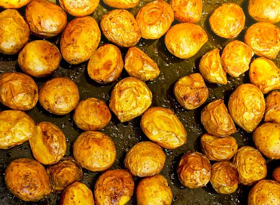 Menší brambory pečeme vcelku, větší raději rozkrojíme.