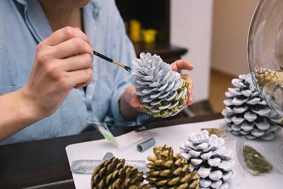 Barvení šišek určených pro vánoční dekorace.
