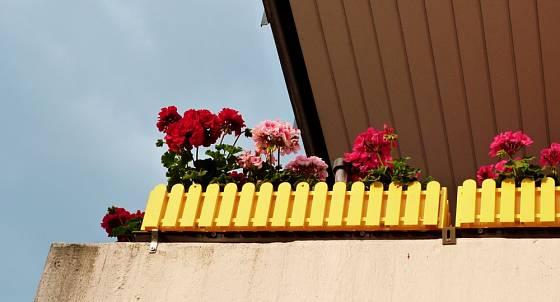 Žlutě natřený dřevěný plůtek.