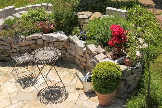Výšený záhon z kamení skvěle ladí k místu zahradního posezení.